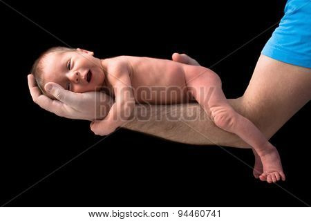 Newborn twins on hands over black background