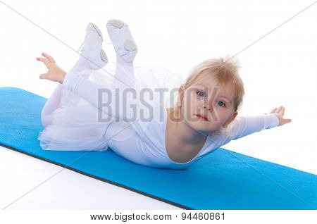 Girl contortionist lies on the gymnastic Mat