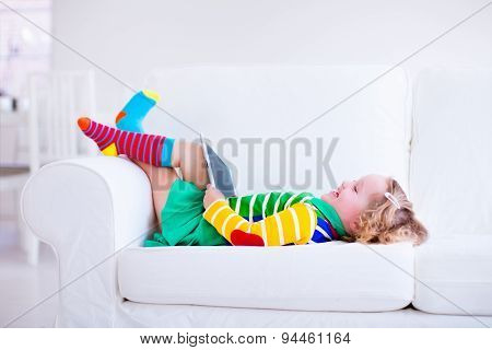 Little Girl With Tablet Computer On A White Couch