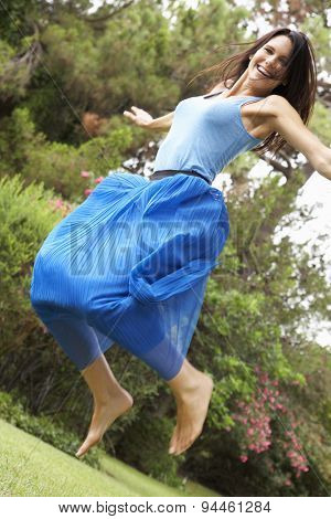 Energetic Woman Jumping In Countryside