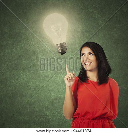Creative Casual Woman Pointing At Lamp