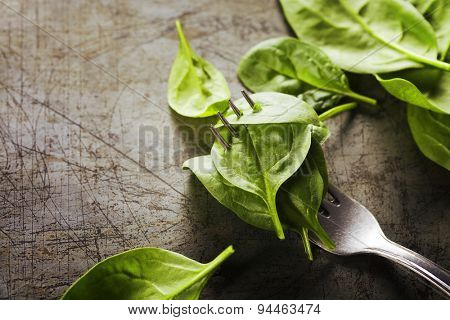 Spinach leaves on a fork - detox, diet or healthy eating concept