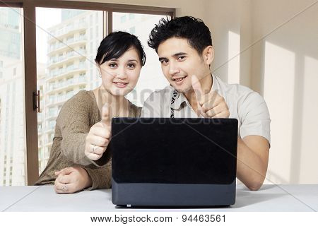 Happy Couple And Laptop Showing Thumbs Up 1