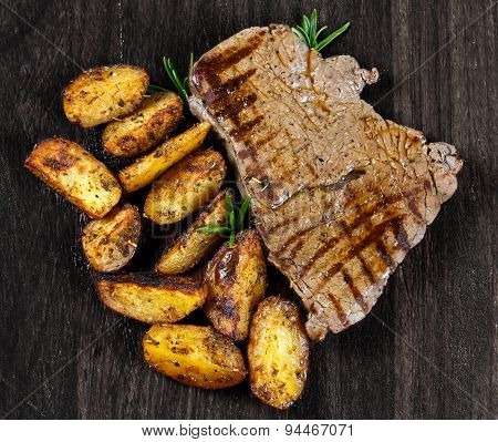 Grilled Beef Steak With Village Potatoes, Rosemary On Wooden Old Board. Background, Texture