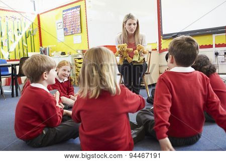 Teacher Telling Story To Elementary School Pupils