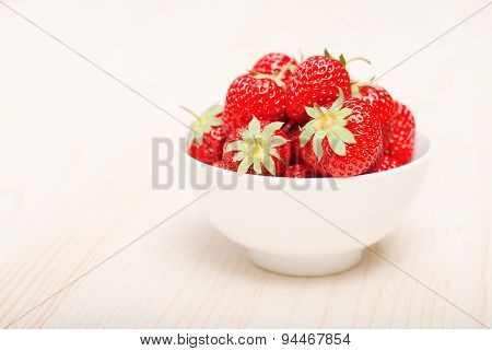 Strawberries In A White Bowl On A Light Table, Side View