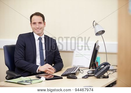 Portrait Of Male Consultant Working At Desk In Office