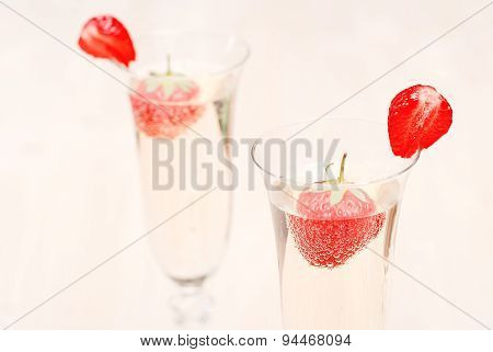 Two Glasses Of Champagne With Strawberry Slices And Whole Strawberries In Champagne