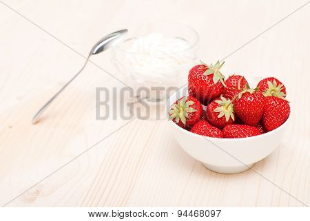 Strawberries In A White Bowl On A Light Table, On The Background Of The Cream In A Transparent Vase