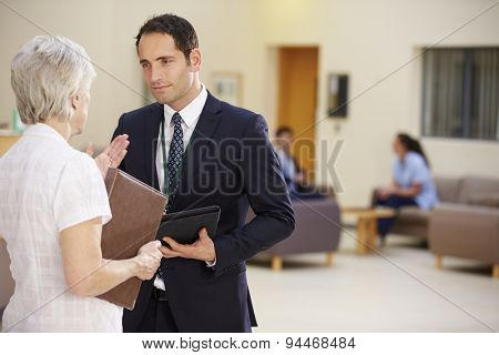 Two Consultants Discussing Patient Notes In Hospital