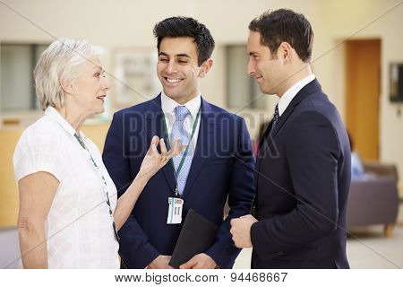 Three Consultants Meeting In Hospital Reception