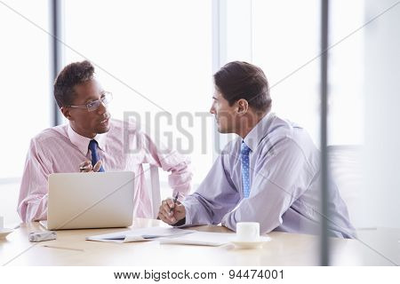 Two Businessmen Working On Laptop At Boardroom Table