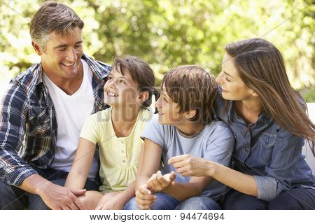 Portrait Of Happy Family Sitting In Garden Together