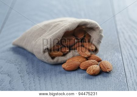 almonds in sack bag on blue wood table