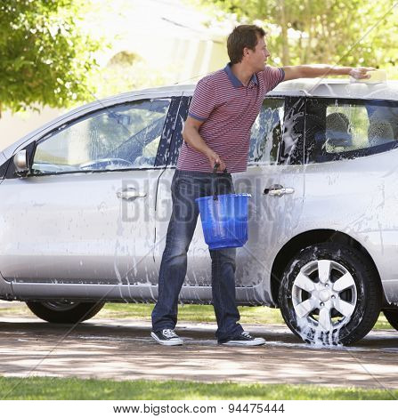 Man Washing Car In Drive