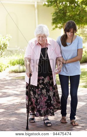 Teenage Granddaughter Helping Grandmother Out On Walk