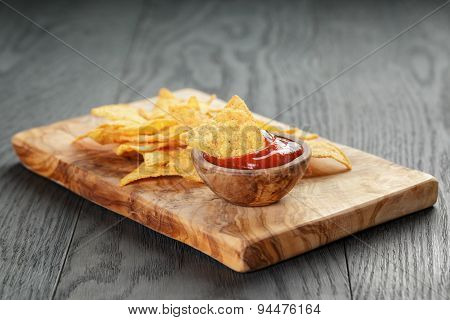 tortilla chips on olive board with tomato sauce, on wooden table
