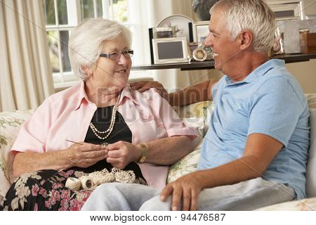 Adult Son Visiting Senior Mother Sitting On Sofa At Home Doing Crochet