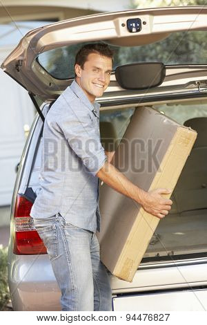 Man Loading Large Package Into Back Of Car