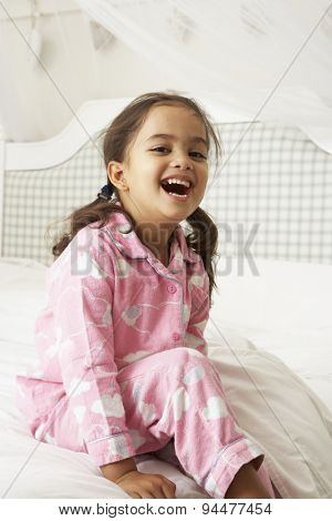 Young Girl Wearing Pajamas Sitting On Bed