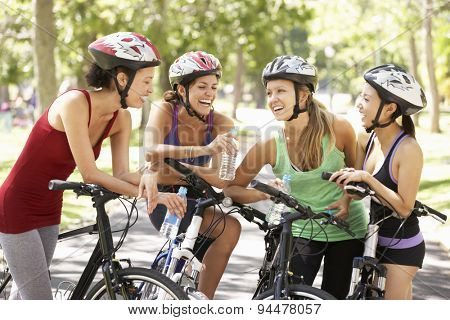 Group Of Women Resting During Cycle Ride Through Park