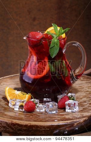 Wine Of Sangrija In A Transparent Jug With A Strawberry, An Orange, Mint And Ice Cubes On A Wooden T