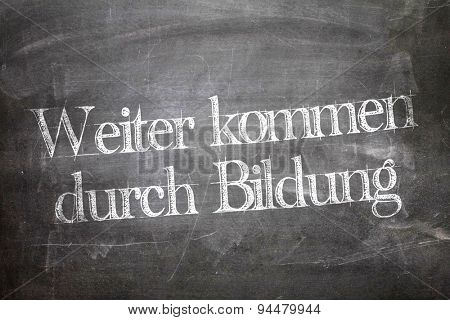 Next come through education (in German) written on a chalkboard
