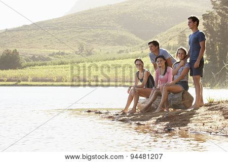 Group Of Young People Relaxing At Shore Of Lake