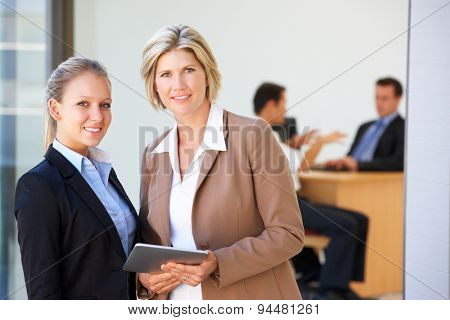 Two Female Executives Using Tablet Computer With Office Meeting In Background