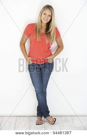 Studio Portrait Of Attractive Young Woman Leaning Against White Background