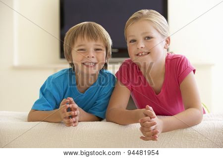Two Children Watching Widescreen TV At Home