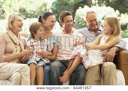 Three Generation Family Sitting On Sofa Together