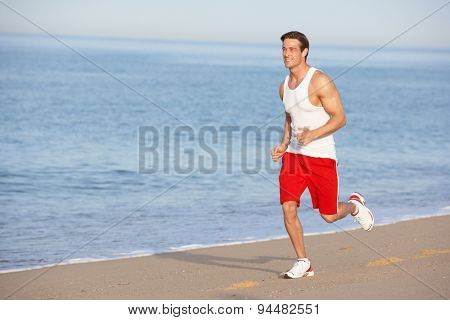 Young Man Jogging Along Beach
