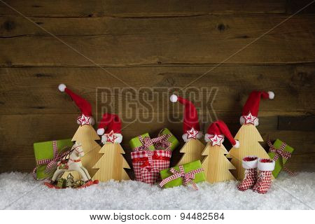 Red, green, yellow and brown christmas background with presents, rocking horse and santa hats on wood with snow.