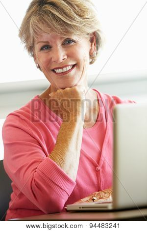 Mature student using computer in class