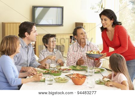 Extended Hispanic Family Enjoying Meal At Home