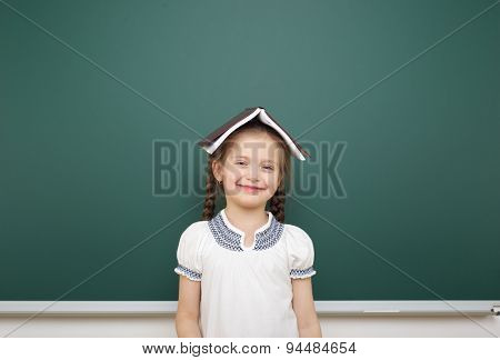 Schoolgirl with book near the school board