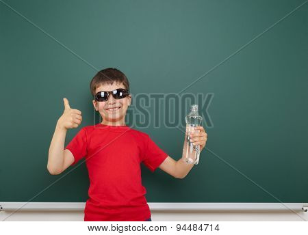 boy with water bottle near the school board