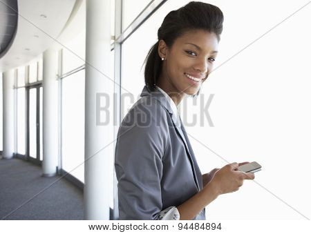 Young Businesswoman Standing In Corridor Of Modern Office Building Using Mobile Phone