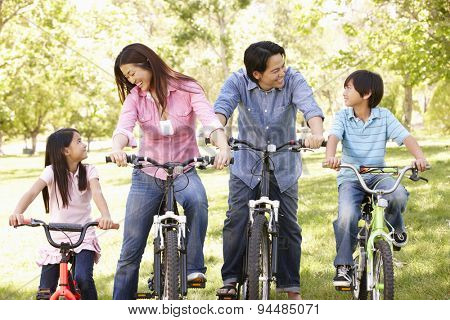 Asian family riding bikes in park
