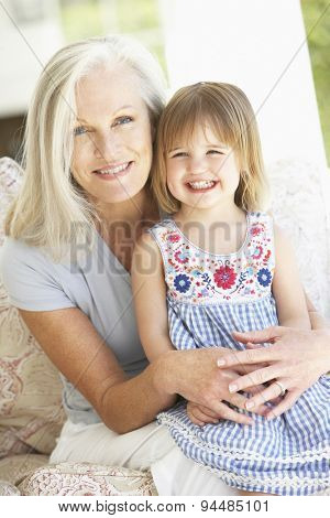 Portrait Of Grandmother And Granddaughter Sitting In Chair