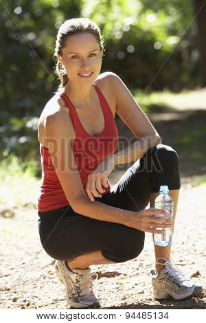 Young Woman Resting Drinking Water After Run