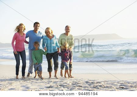 Three Generation Family On Holiday Walking Along Beach
