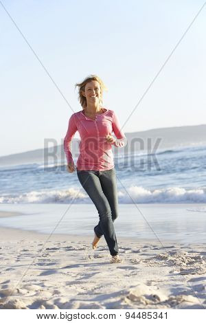Young Woman Running Along Sandy Beach On Holiday