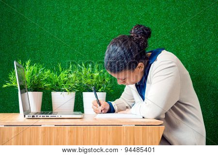 Young woman, sitting at a desk with a laptop in front of her, concentrated, writing down notes on a note pad