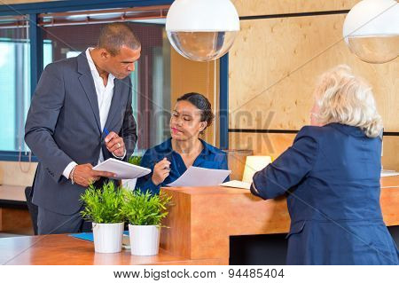 Coworkers discussing small matters with a secretary at a reception desk of a large corporate company