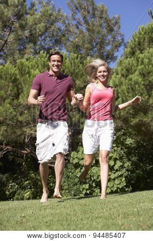 Young Couple Running Through Summer Field