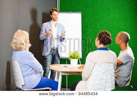 Young associate giving a presentation, using a flip-over white board and markers, to a small project team in an informal setting during a project team meeting in the lounge of a modern office
