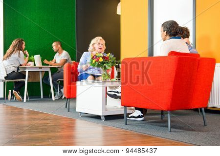 Several people sitting in a business lounge during informal meetings and project team conferences