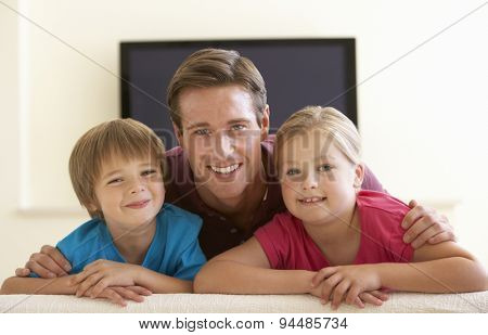Father And Children Watching Widescreen TV At Home